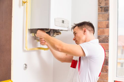 Plombier Auriol - Un plombier répare un chauffe eau