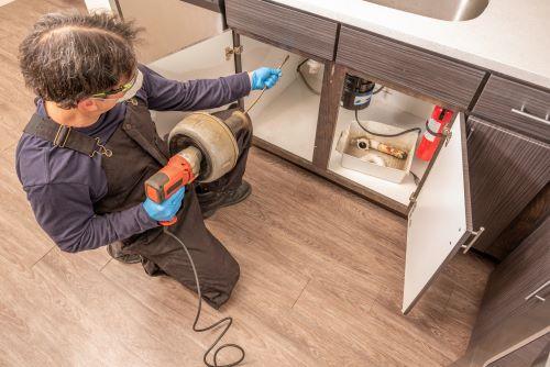 Plombier Feyzin - Un plombier fait des travaux dans une cuisine.