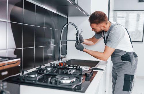 Plombier Feyzin - Un plombier installe un mitigeur dans une cuisine.