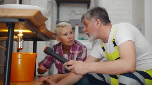 Plombier Gruson - Un plombier et une cliente constate une fuite d'eau sous un lavabo