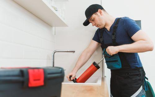 Plombier Gruson - Un plombier effectue un débouchage dans un évier dans cuisine