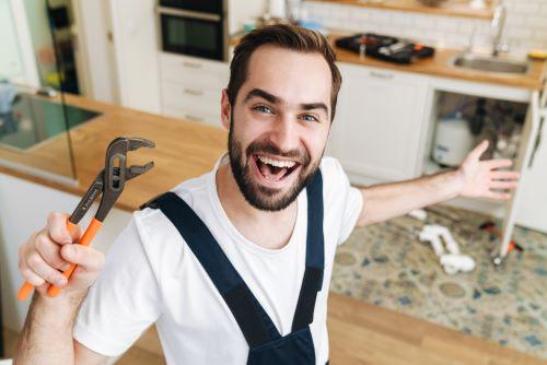 Plombier Irigny - Un plombier heureux répare un évier.