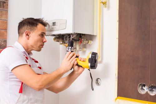 Plombier La Ciotat - Un plombier répare un chauffe eau