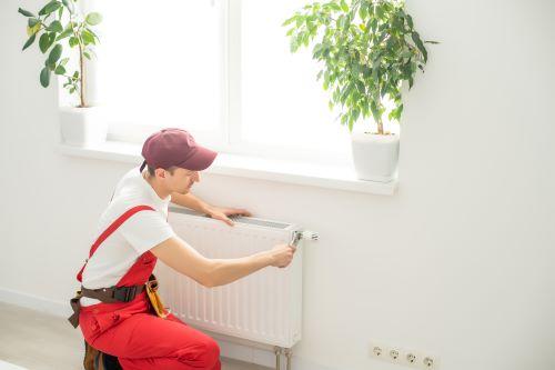 Plombier La Destrousse - Un plombier installe un chauffage mural