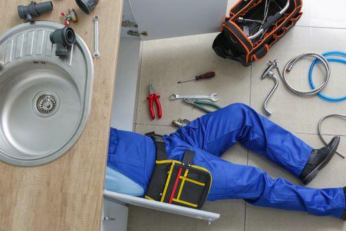 Plombier La Madeleine - Un plombier effectue des réparations sur un évier dans une cuisine