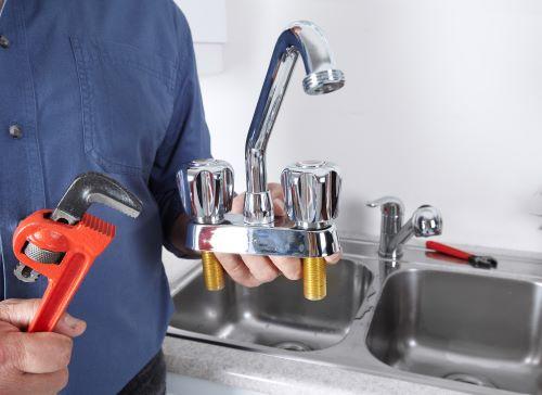 Plombier Lambersart - Un plombier installe un nouveau robinet d'évier