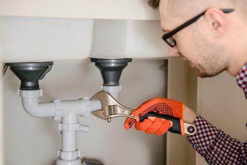 Plombier Lezennes- Un plombier monte un siphon