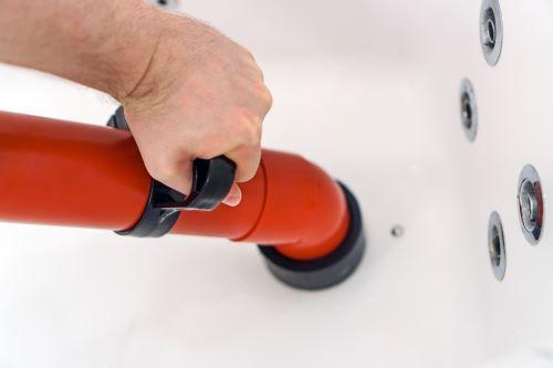 Plombier Lompret - Un plombier effectue un débouchage