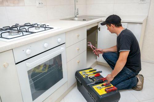 Plombier Lyon 1 - Un plombier répare l'évier d'une cuisine