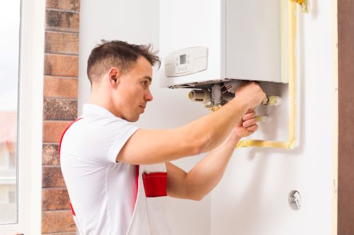Plombier Lyon 1 - Un plombier répare une chaudière