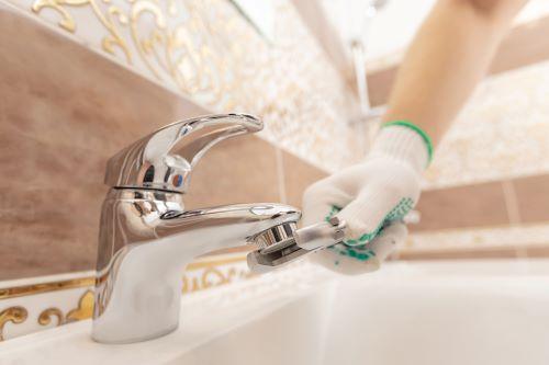 Plombier Lyon - Un plombier répare un robinet de salle de bain