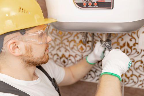 Plombier Lyon - Un plombier répare un chauffe eau