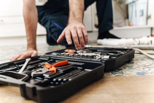 Plombier Lyon - Un plombier prend ses outils de réparation