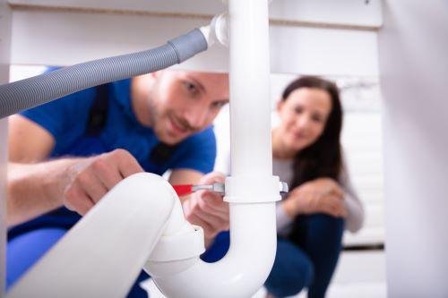 Plombier Lyon 8 - Un plombier change un siphon sous les yeux de la cliente