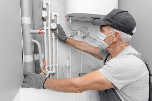 Plombier Marignane - Un plombier intervient sur un chauffe eau