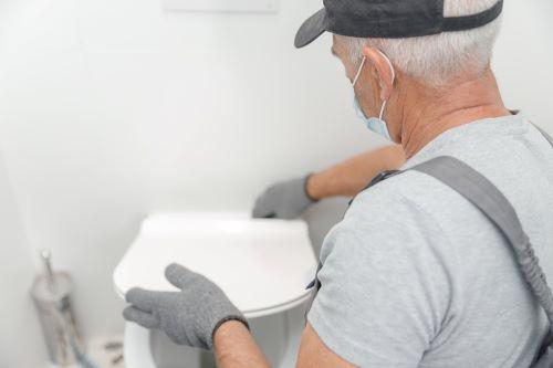 Plombier Marseille - Un plombier installe un WC