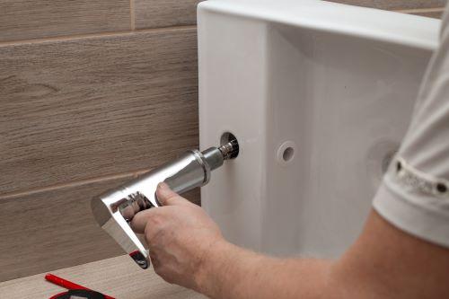 Plombier Marseille - Un plombier installe le robinet d'un lavabo
