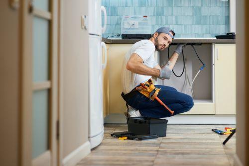 Plombier Marseille - Un plombier installe un nouvel évier dans une cuisine
