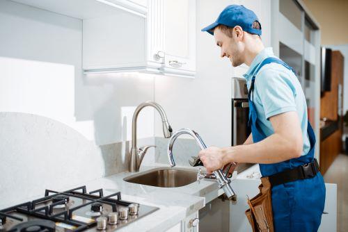 Plombier Marseille - Un plombier installe un évier dans une cuisine