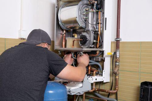 Plombier Paris - Un plombier répare un cumulus