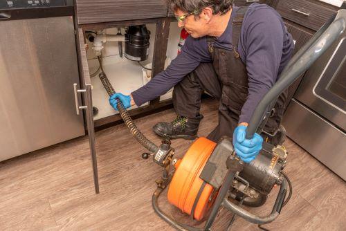 Plombier Paris 4 - Un plombier procède au débouchage d'un évier