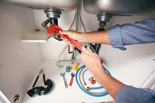 Plombier Paris 8 - Un plombier intervient sur la tuyauterie d'un évier