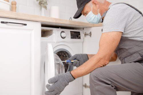 Plombier Peypin - Un plombier répare une machine à laver