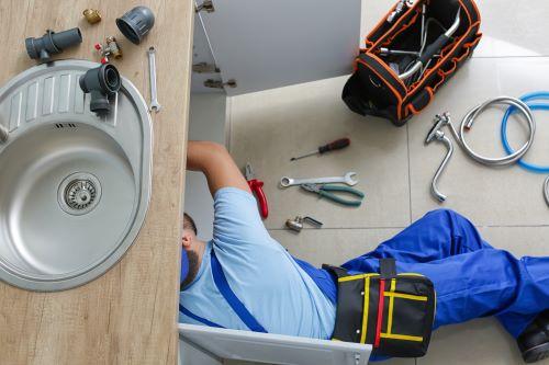 Plombier Phalempin - Un plombier répare un robinet.