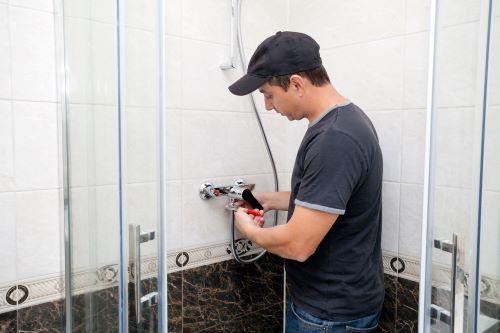 Plombier Ronchin - Un plombier installe un robinet de douche