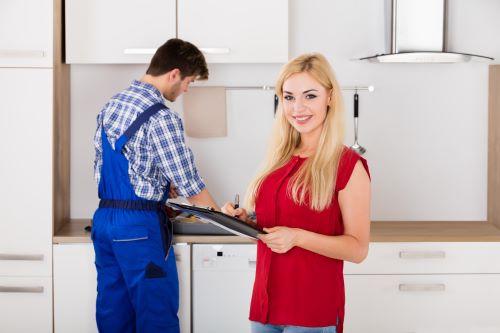 Plombier Ronchin - Une femme signe son devis pendant que le plombier travaille