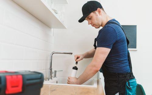 Plombier Sathonay-Camp - Un plombier débouche l'évier d'une cuisine