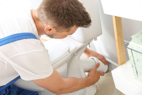 Plombier Toufflers - Un artisan installe des toilettes.