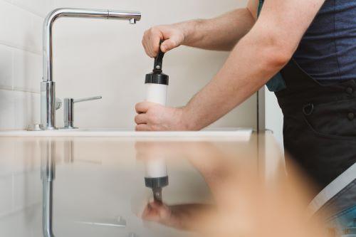 Plombier Verlinghem - Un plombier effectue le débouchage d'un évier
