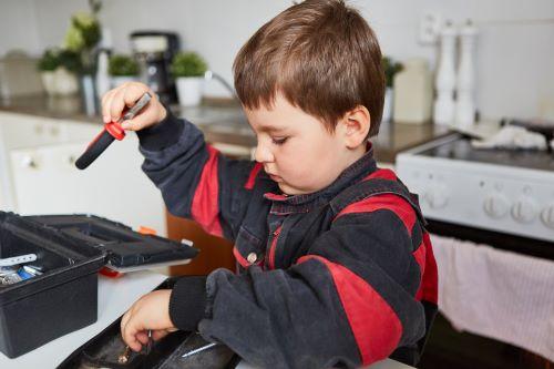 Plombier Vitrolles - Un enfant tient les outils du plombier
