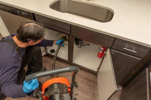 Plombier Wattignies - Un plombier effectue le débouchage d'un évier dans une cuisine