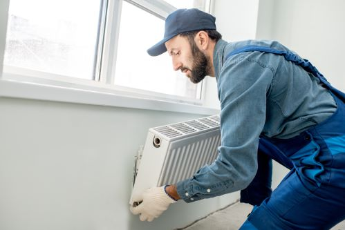 chauffagiste Cherbourg-en-Cotentin - un plombier chauffagiste installe un radiateur