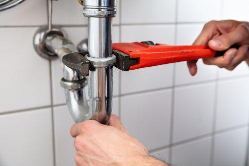 plombier Combs-la-Ville - un artisan desserre le siphon d'un robinet