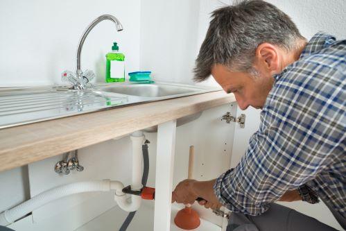 plombier Loos - un homme débouche un siphon d'évier