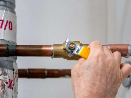 plombier Paris 5 - un artisan ferme une vanne d'arrivée d'eau