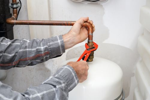 Plombier Nice - Un plombier répare un chauffe-eau